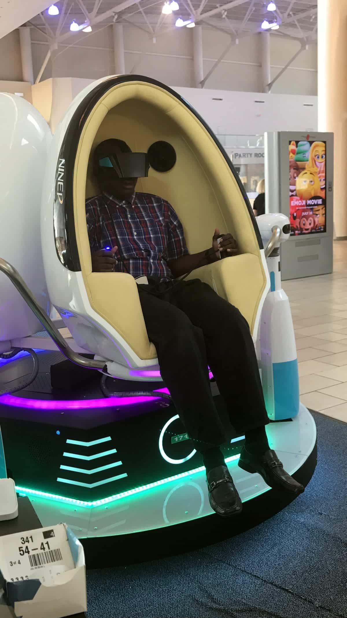 A photo of a man sitting in a VR simulator.