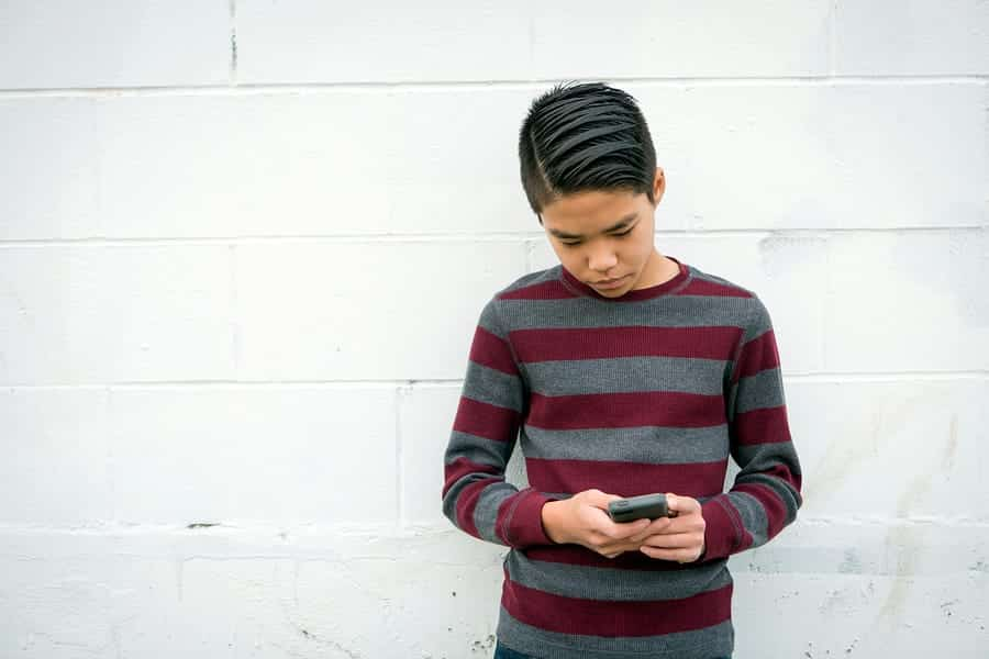 A photo of a teenage boy looking at his smartphone.
