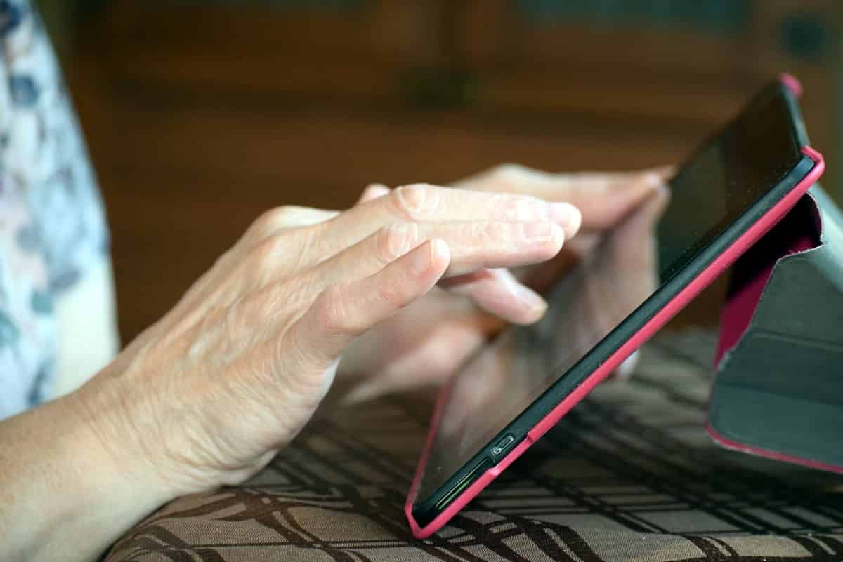 A photo of an older person using a tablet in a pink case.