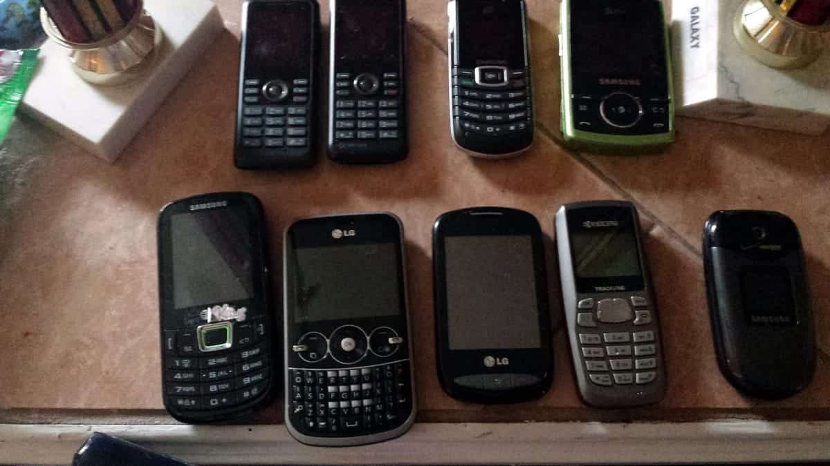 A photo of various old cell phones on a table.