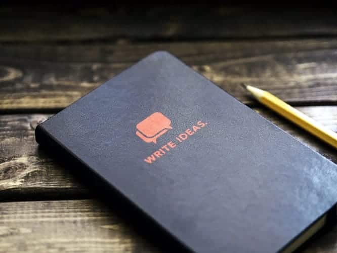 "An image of a notebook that says ""write ideas"" on a wooden table with a pencil."