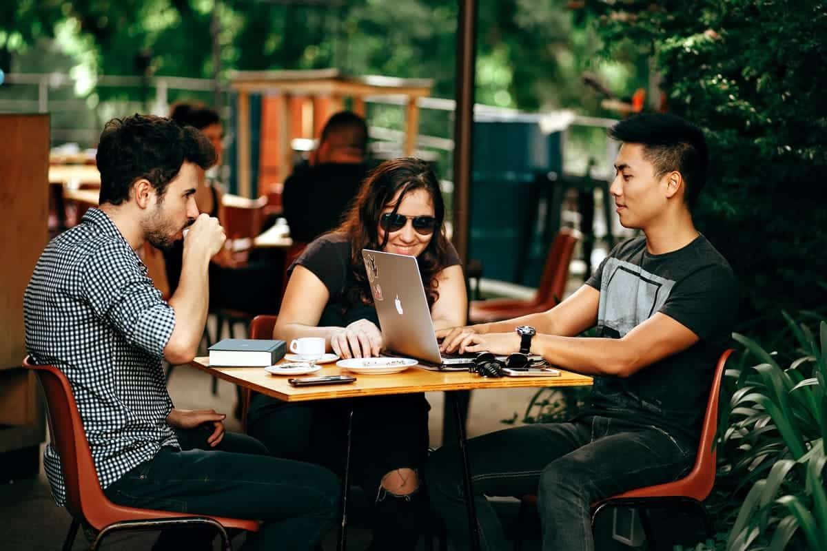 Three people meeting around a table, drinking coffee, and working on a laptop.