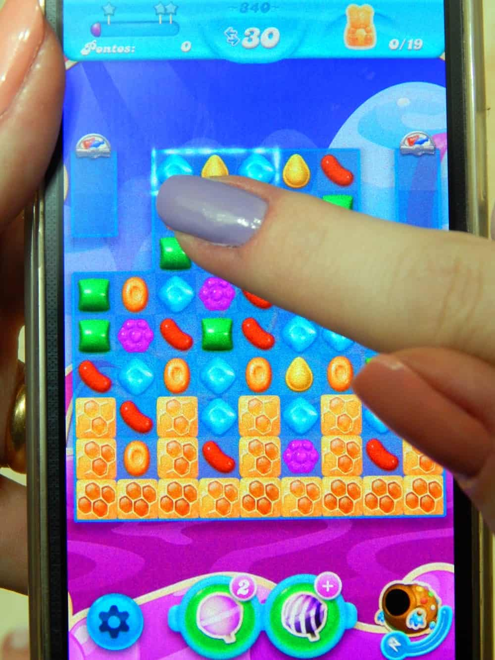 A photo of a person playing candy crush on their smartphone.