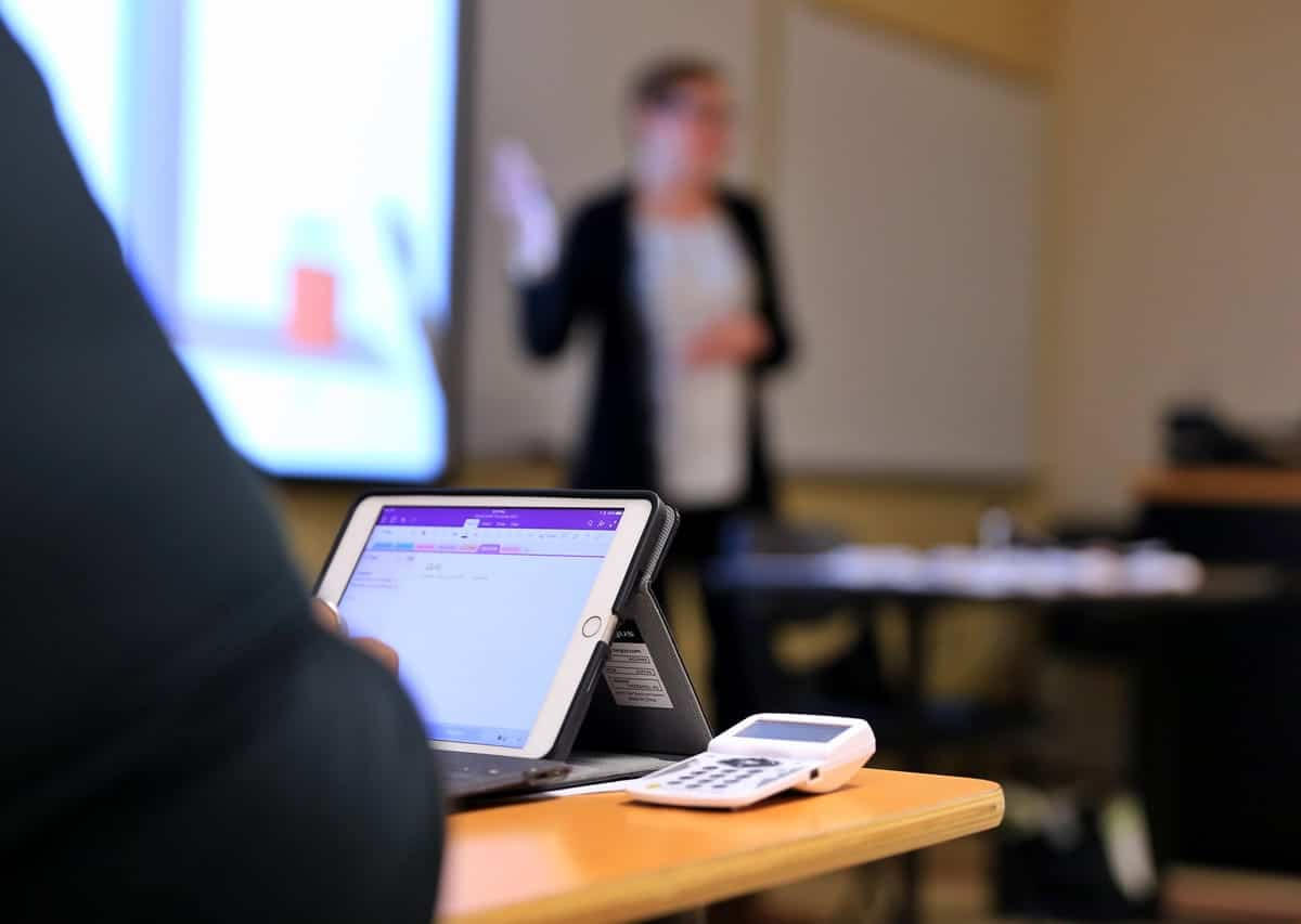 A photo of a student using an iPad to take notes during a presentation.