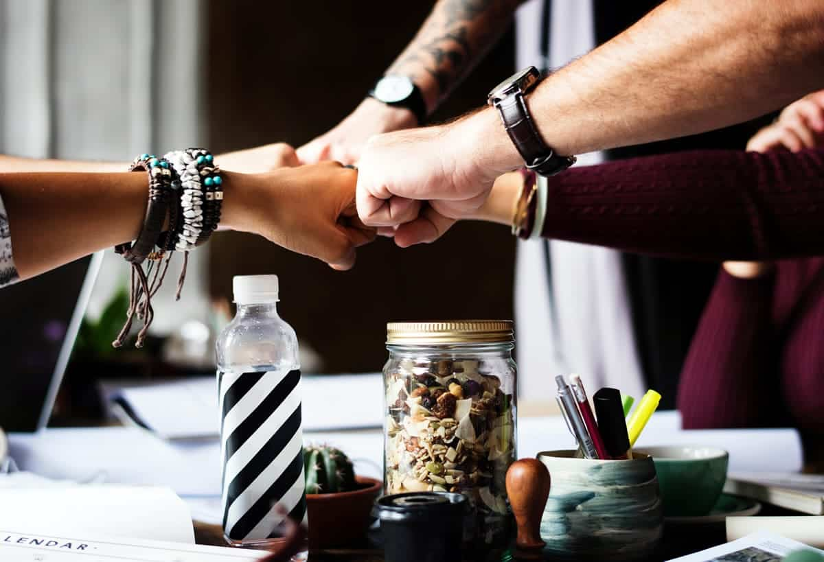 Teammates bringing hands together to show teamwork.