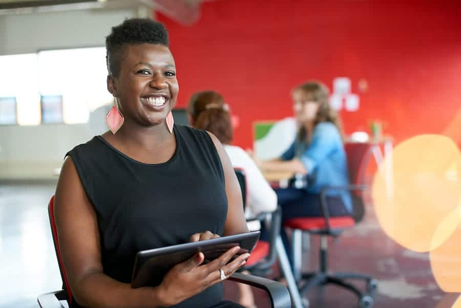 A photo of a smiling woman holding a tablet.