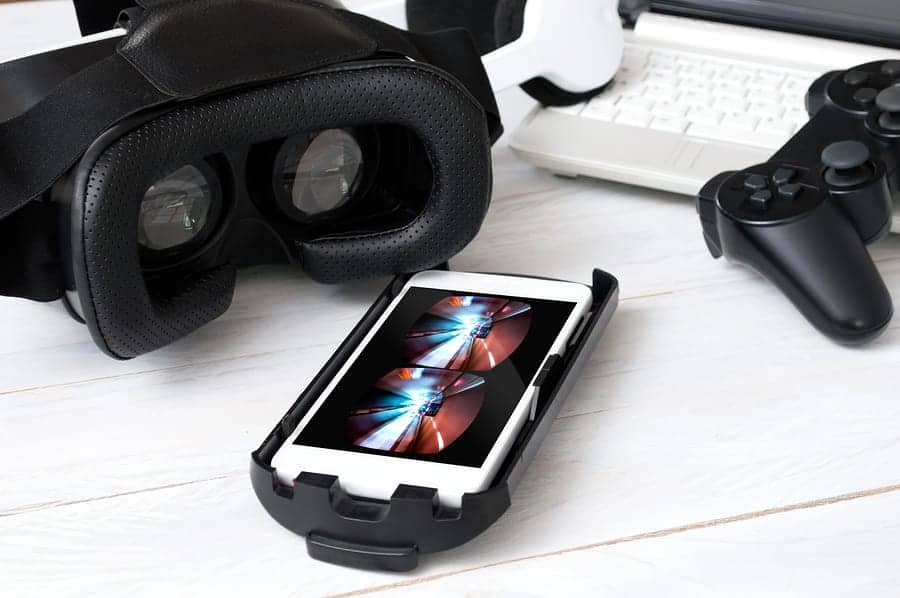 A photo of a VR headset on a table with a smartphone and a video game controller.