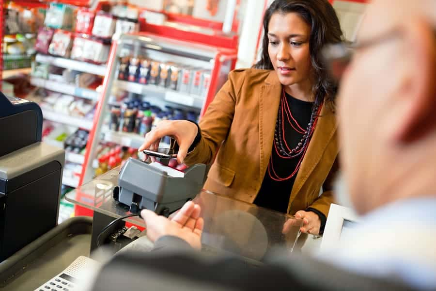 A photo of a woman using her smartphone's mobile pay feature at a retail store.