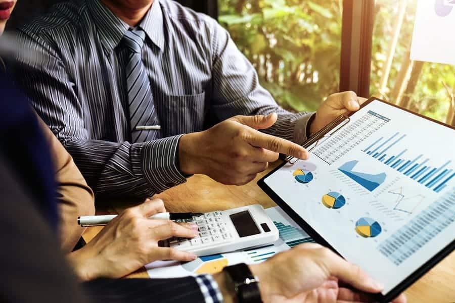 A photo of investors looking at charts and graphs.