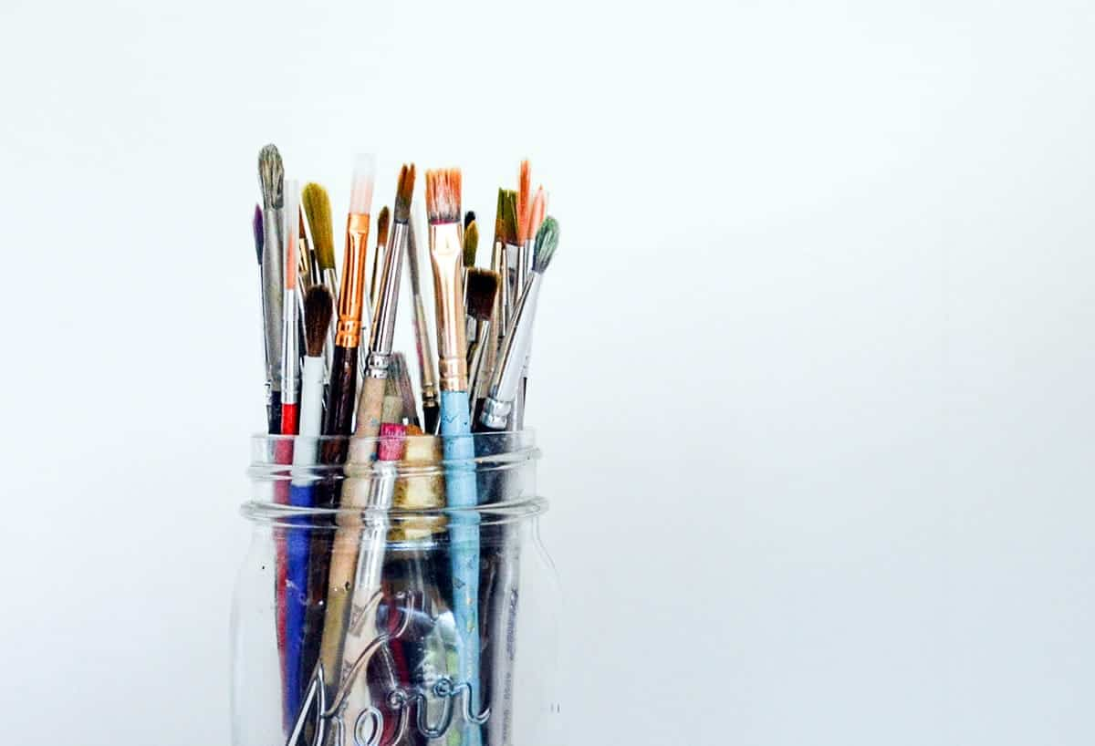 Several paintbrushes in a glass jar.