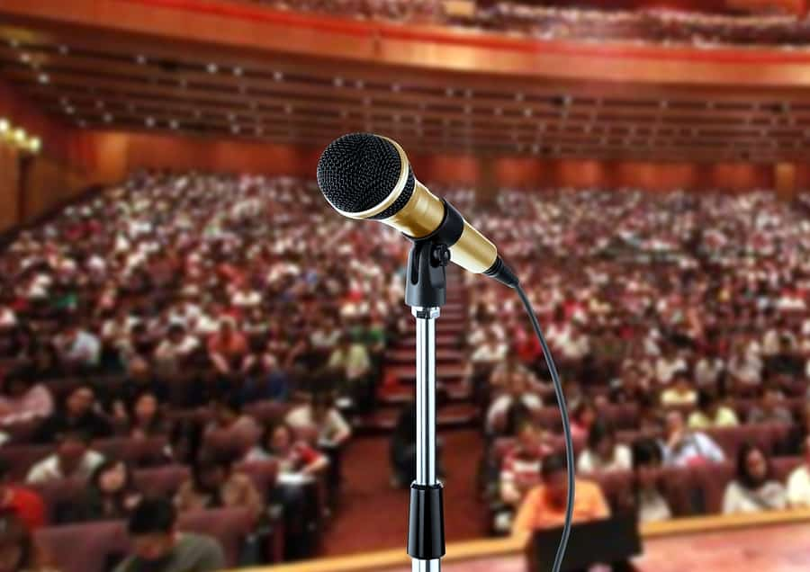 A close-up photo of a microphone on a mic stand with a large audience in the background.