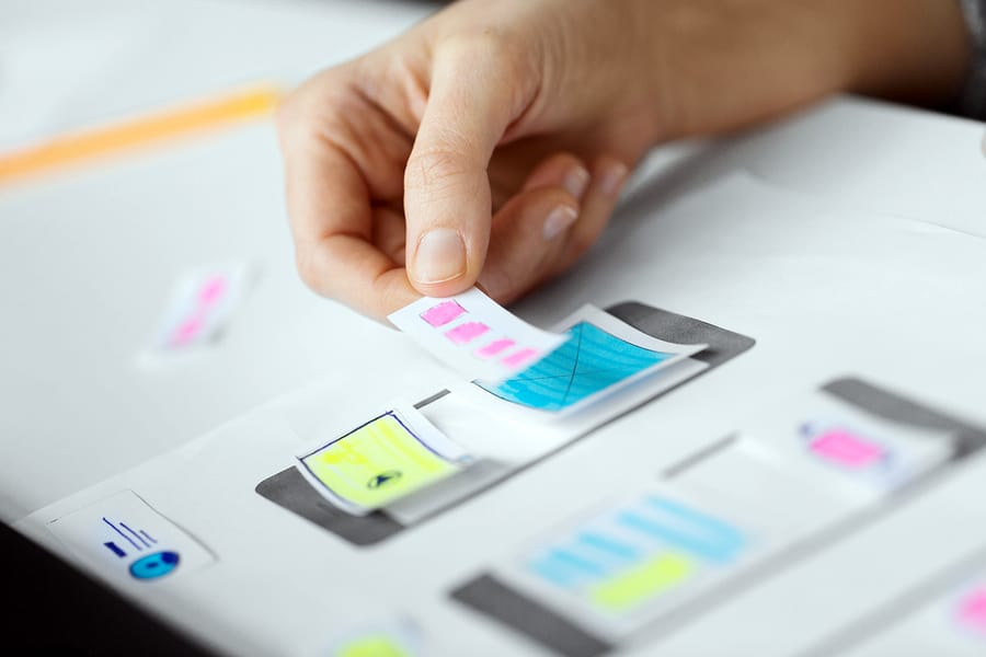 A close-up photo of a person placing pieces of paper onto a drawing of a mobile phone, demonstrating mobile app design decisions.