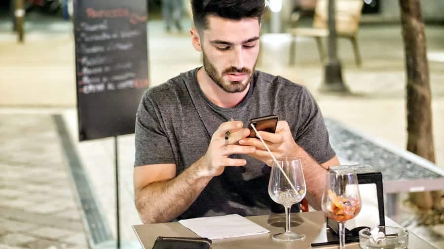 A photo of a man on a restaurant patio checking his smartphone.