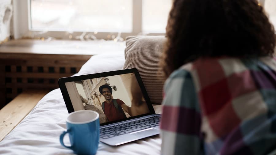 A photo of a woman having a video call with someone through her laptop.