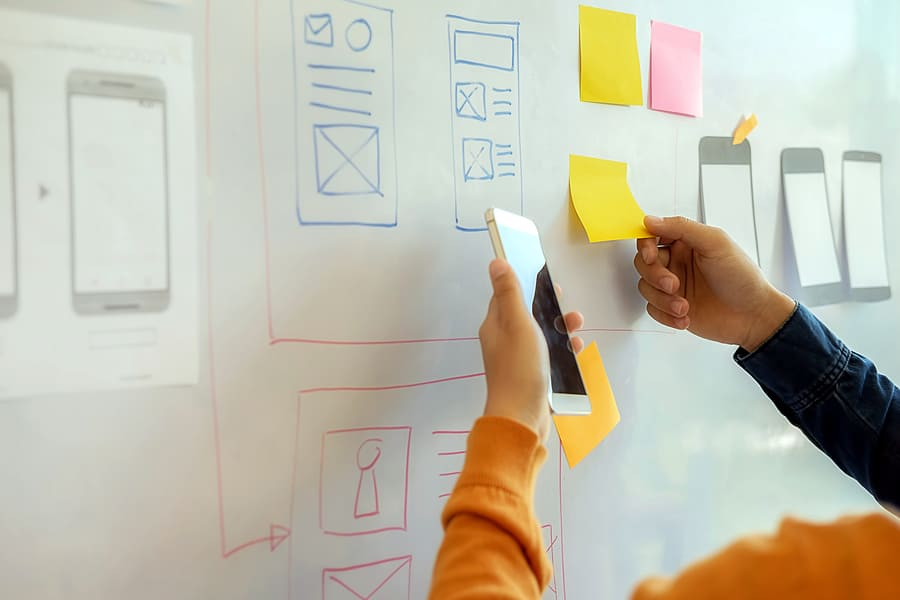 A photo of people moving sticky notes around on a whiteboard.