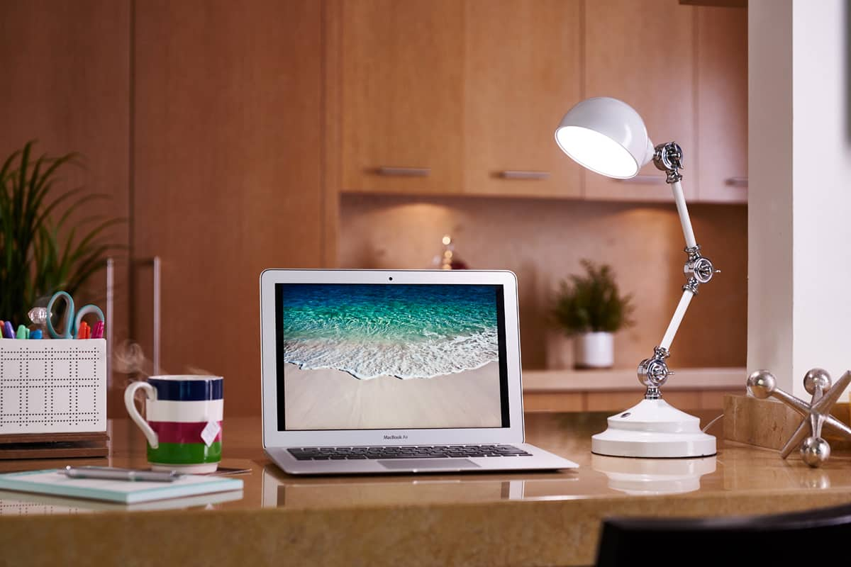 A photo of the OttLite LED Revive Desk Lamp on a desk next to a laptop and a mug of hot tea.