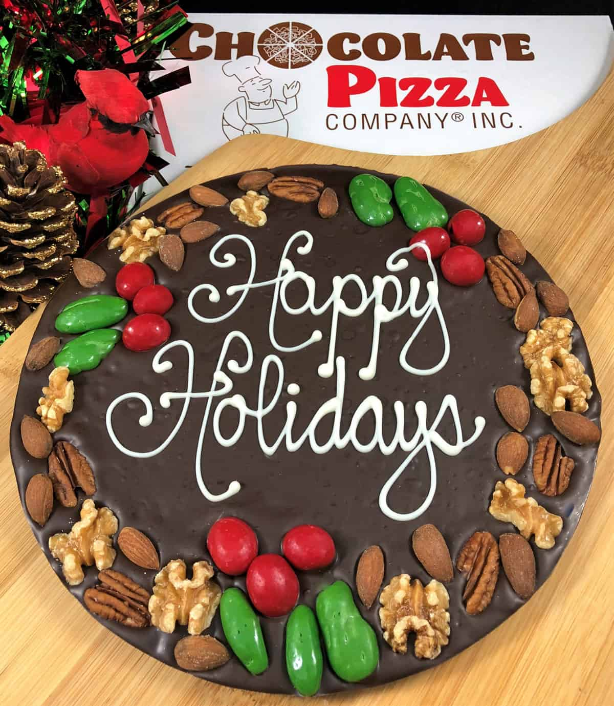 "A photo of a chocolate pizza with ""Happy Holidays"" written on it and decorated with a border made of pecans, walnuts, and almonds."