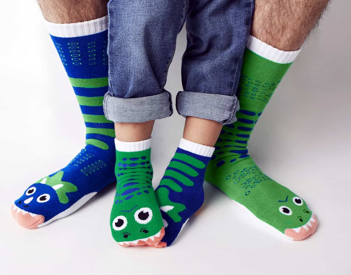 A photo of an adult and a child wearing the T-rex and Triceratops socks from Pals Socks.