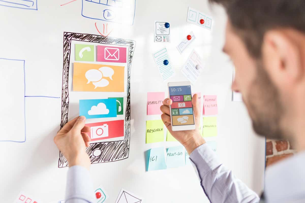 A photo of a mobile app designer experimenting with layout using paper cutouts on a whiteboard.