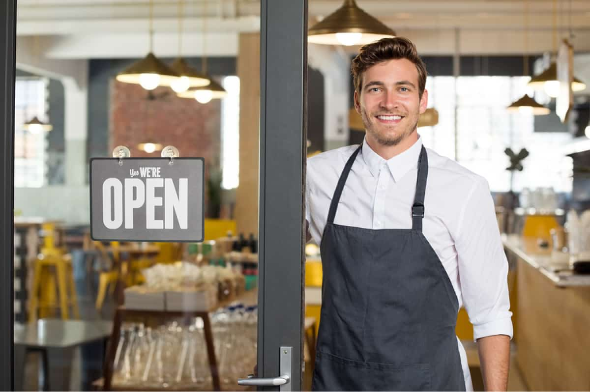 "A photo of a man standing next to an ""open"" sign with a proud smile on his face."
