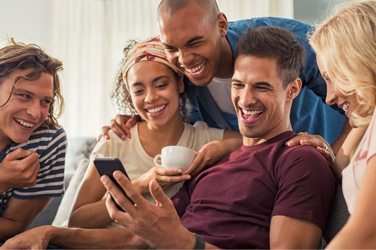 A photo of a man showing a group of friends his latest mobile app design.