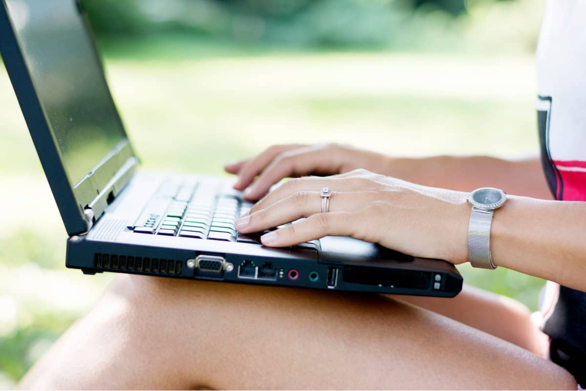 A photo of a laptop being balanced on a woman's knees as she works in a park.