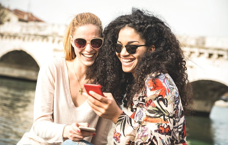 A photo of two women looking at a smartphone and laughing together.
