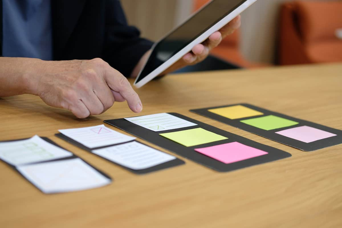A photo of a mobile app designer using sticky notes to work on his mobile app layout.