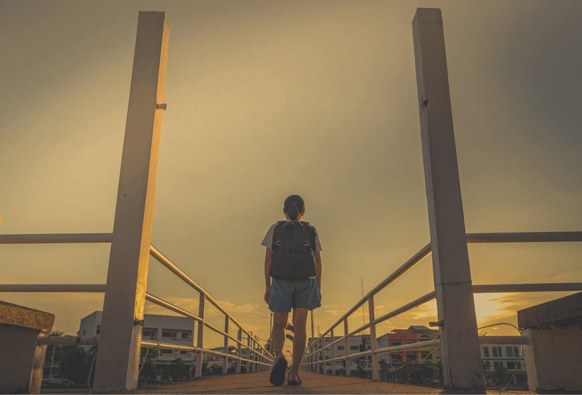 A photo of a woman walking alone on a bridge at dusk.