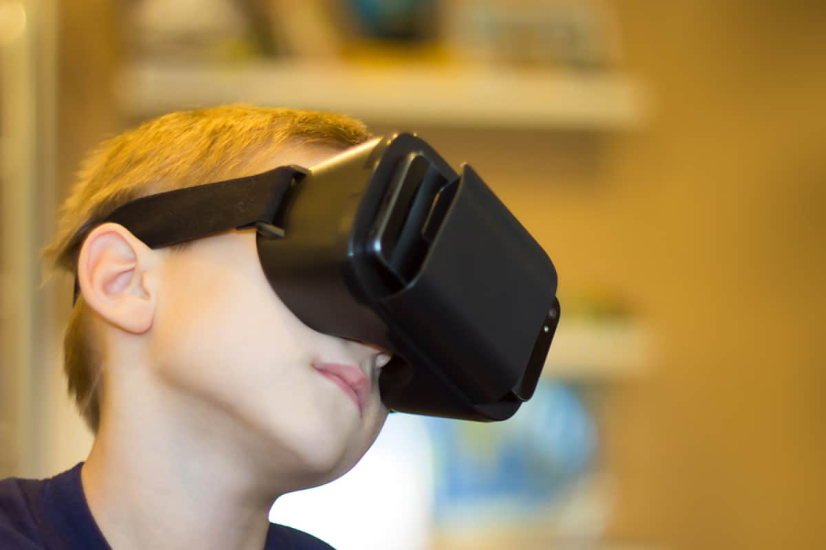 A photo of a young boy wearing a virtual reality headset.