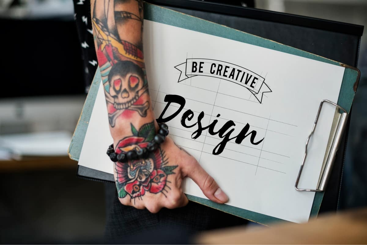 """A person with tattoos on their arm holding a clipboard that says """"be creative design."""""""