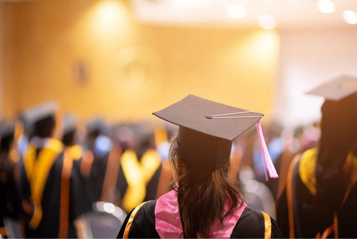 A photo taken from behind a graduate watching a commencement ceremony.