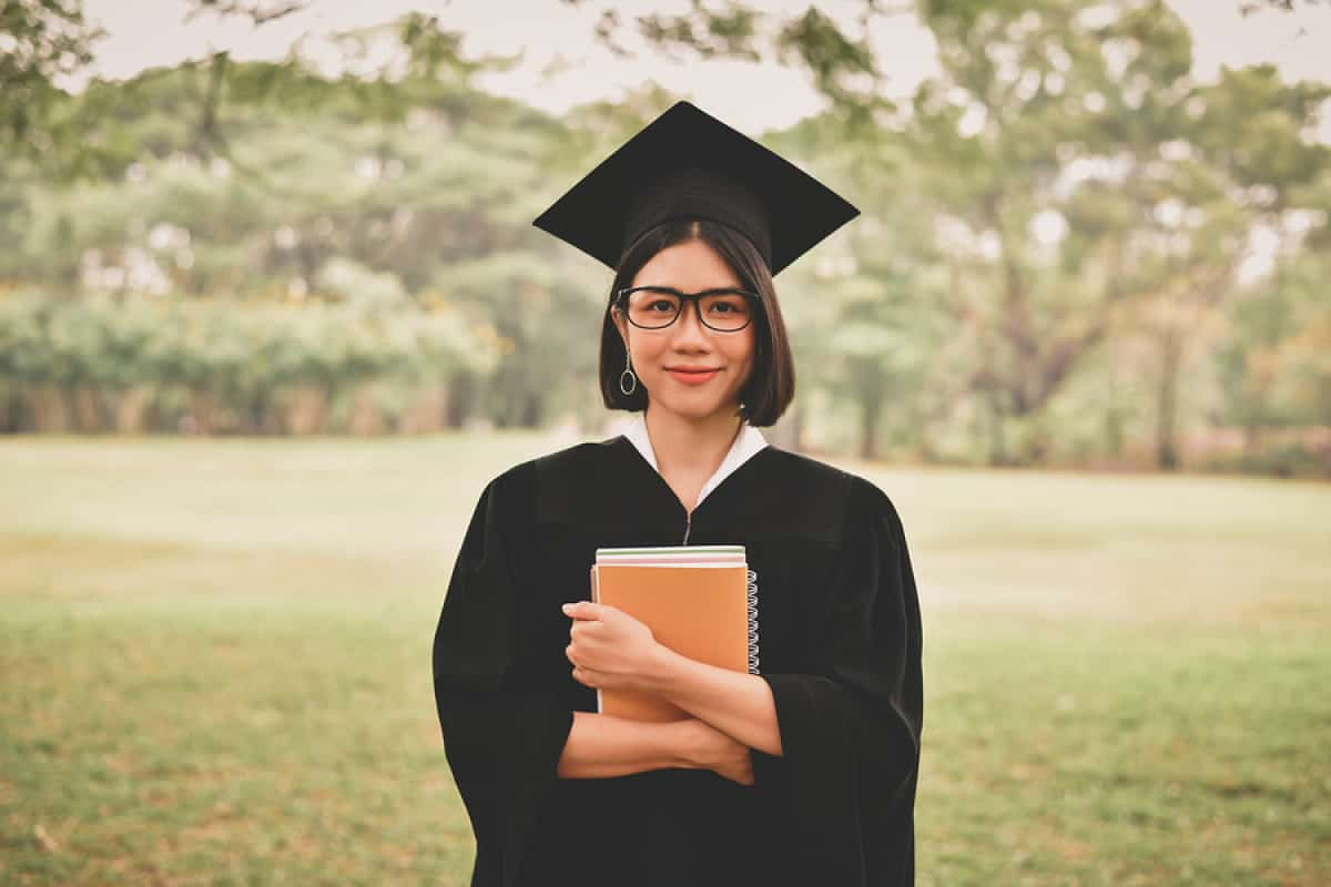 A photo of a happy graduate holding a notebook to her chest.