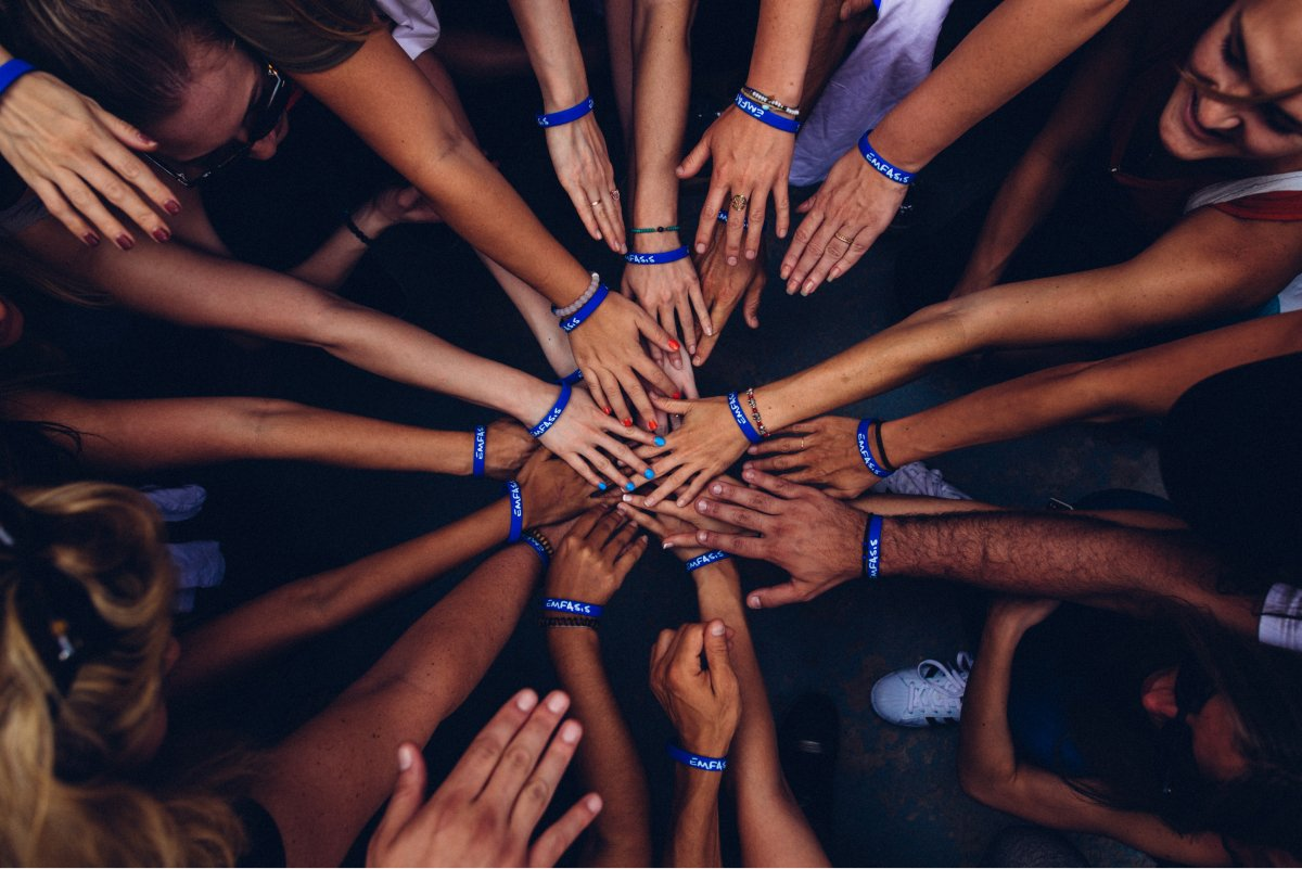 A top-down view of multiple team members putting their hands into a circle.