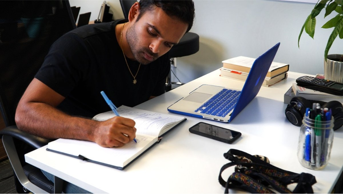 A photo of Fracture co-founder and CEO Abhi Lokesh working at his desk.