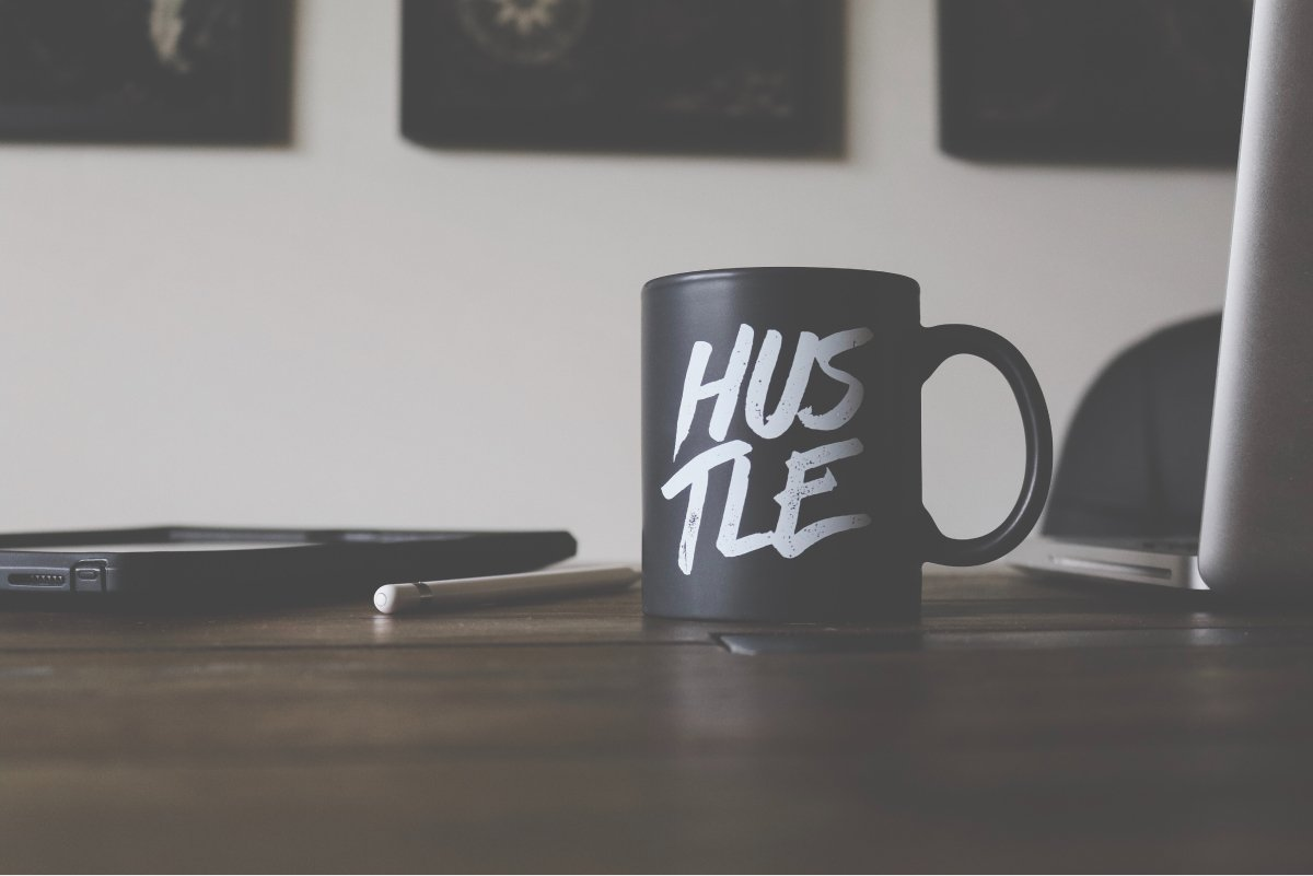 "A photo of a coffee mug that says ""HUSTLE"" sitting on a desk with a laptop and a tablet."