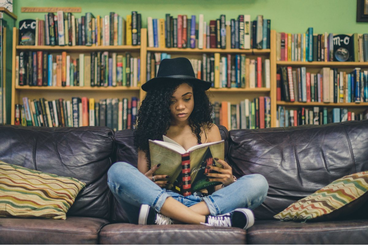 A photo of a college student reading a book on a leather couch in a library.