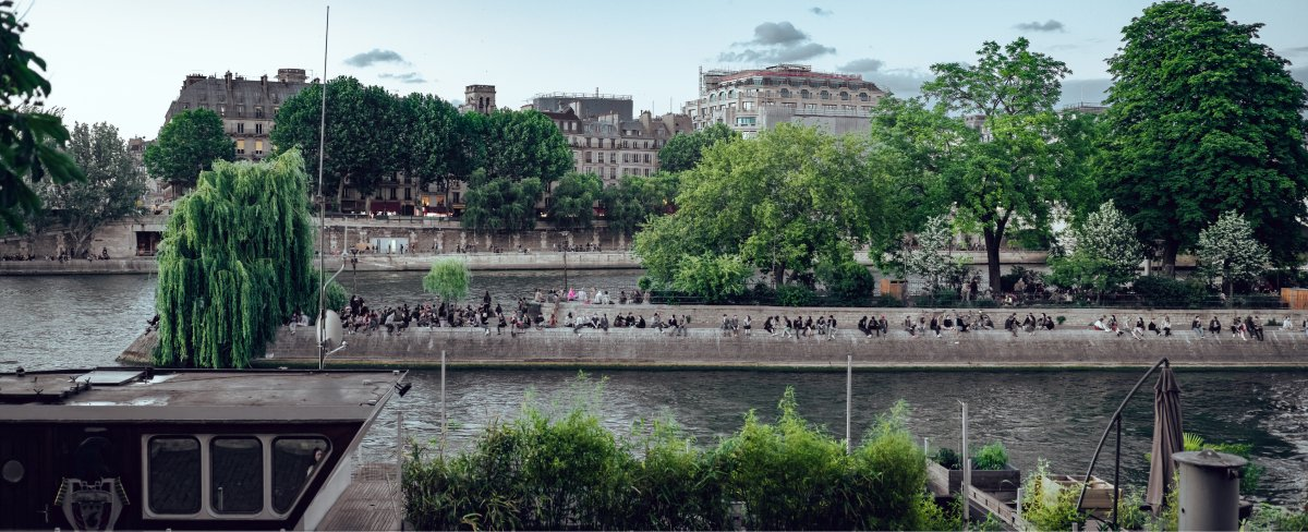 A photo of people sitting in a park in the middle of a city on a river.