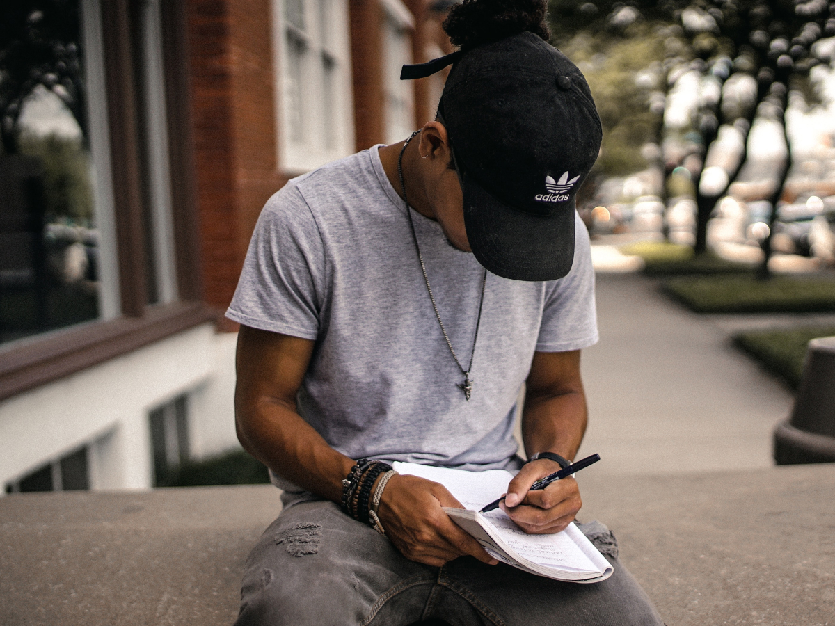 A photo of a college student sitting on a ledge taking notes in a notebook.