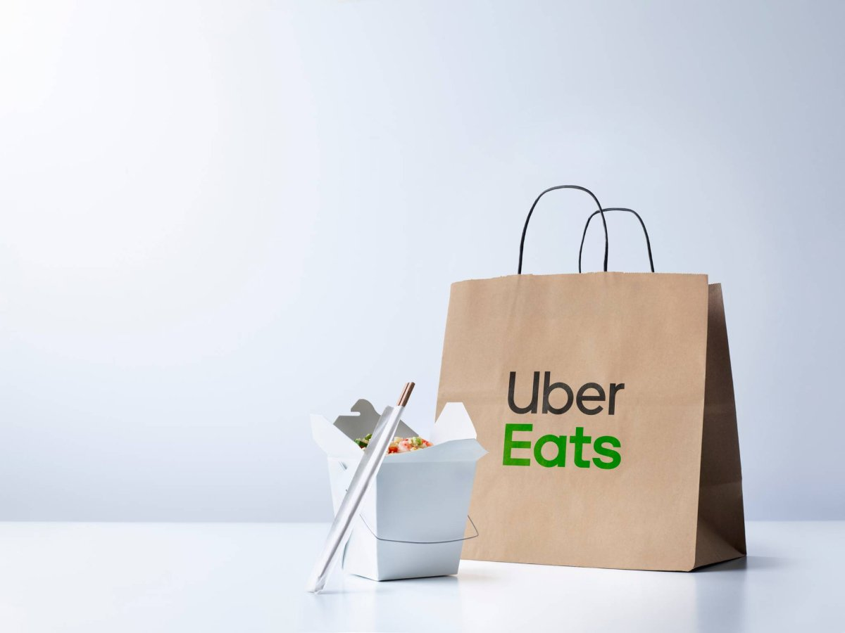 A photo of an open takeout container on a table with chopsticks and an UberEats paper bag.