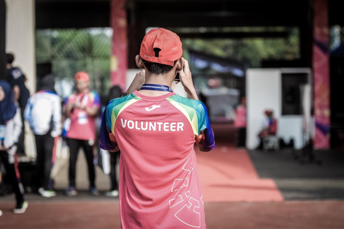 """A photo of a person from behind wearing a shirt that says """"volunteer."""""""
