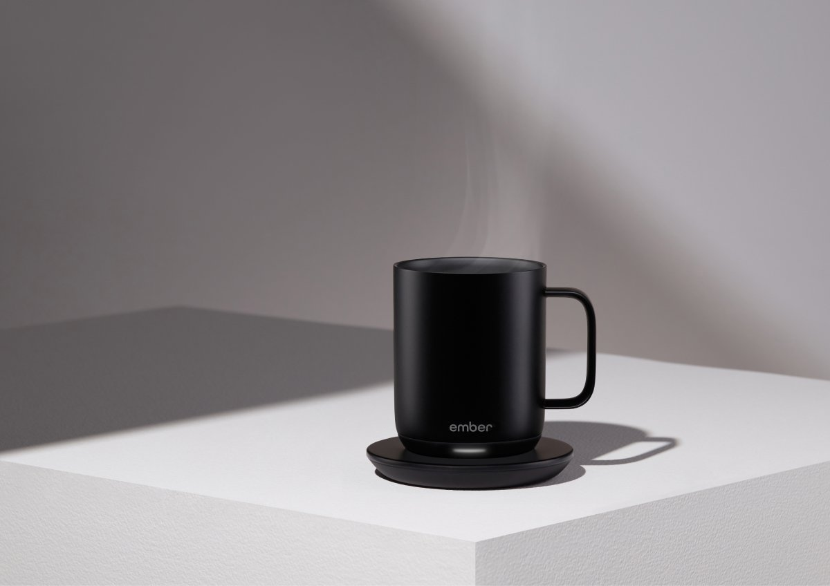 A photo of an Ember mug full of piping hot coffee sitting on a charging coaster.