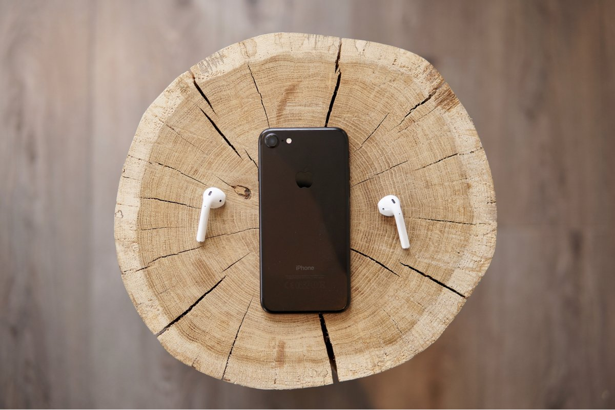 A photo of Apple AirPods sitting next to an iPhone.