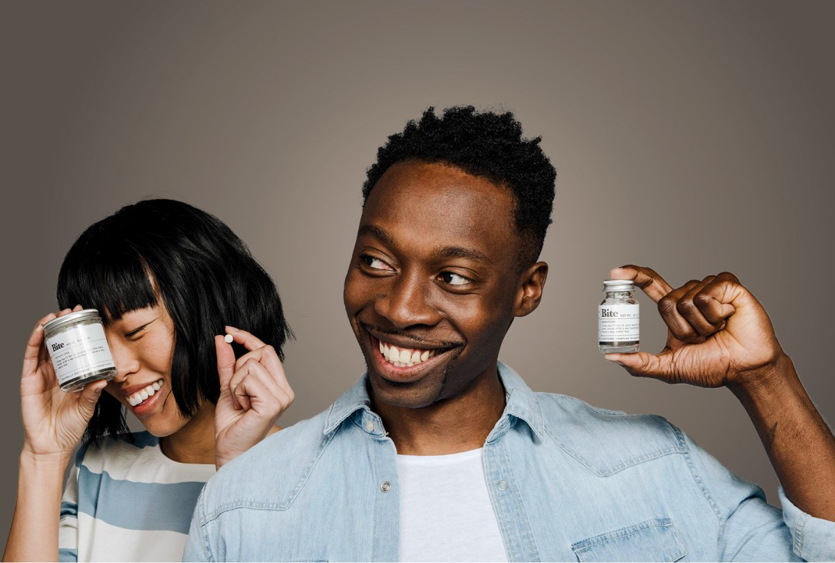 A photo of two people holding bottles of Bite toothpaste bits.