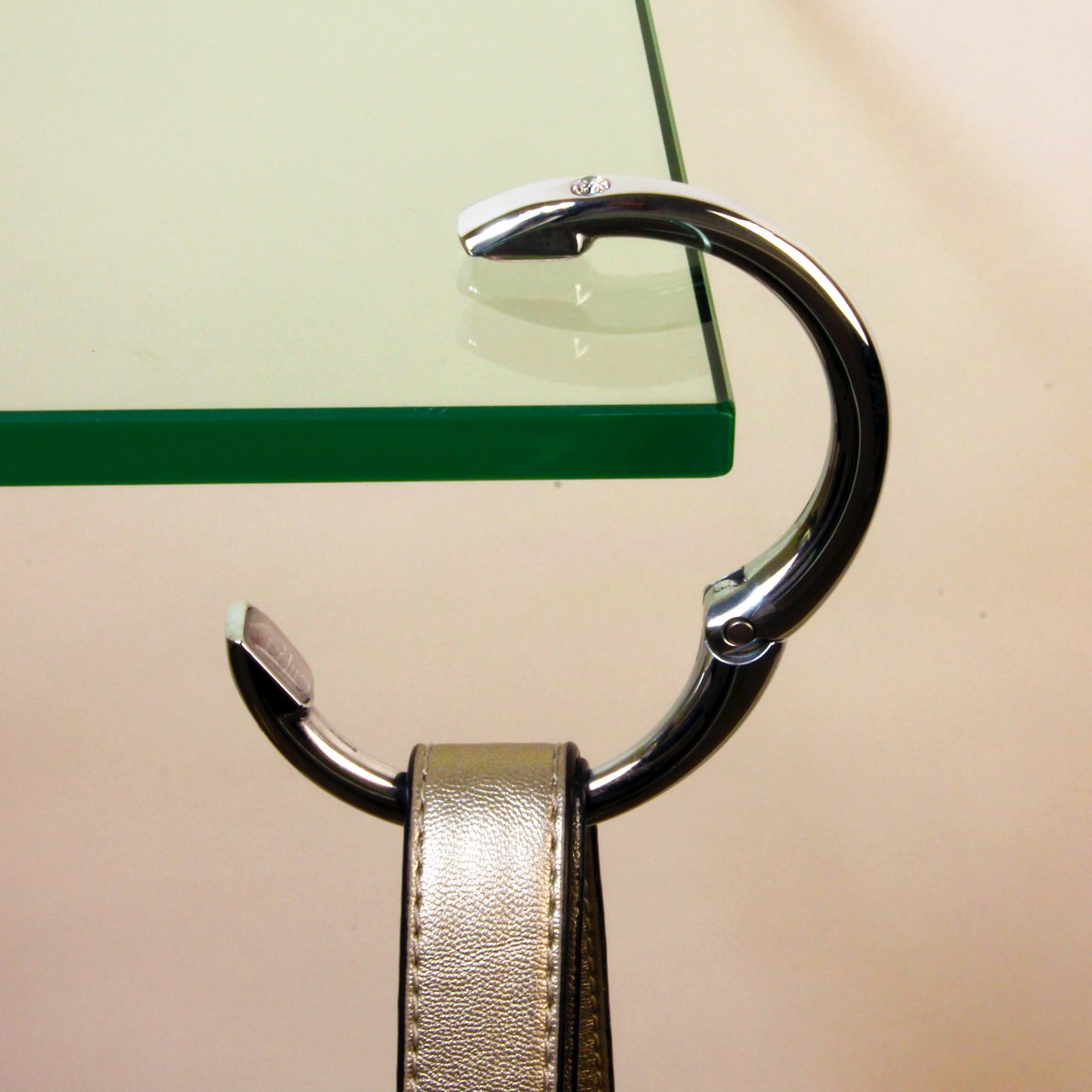 A photo of a Clipa holding up a purse on a glass table.