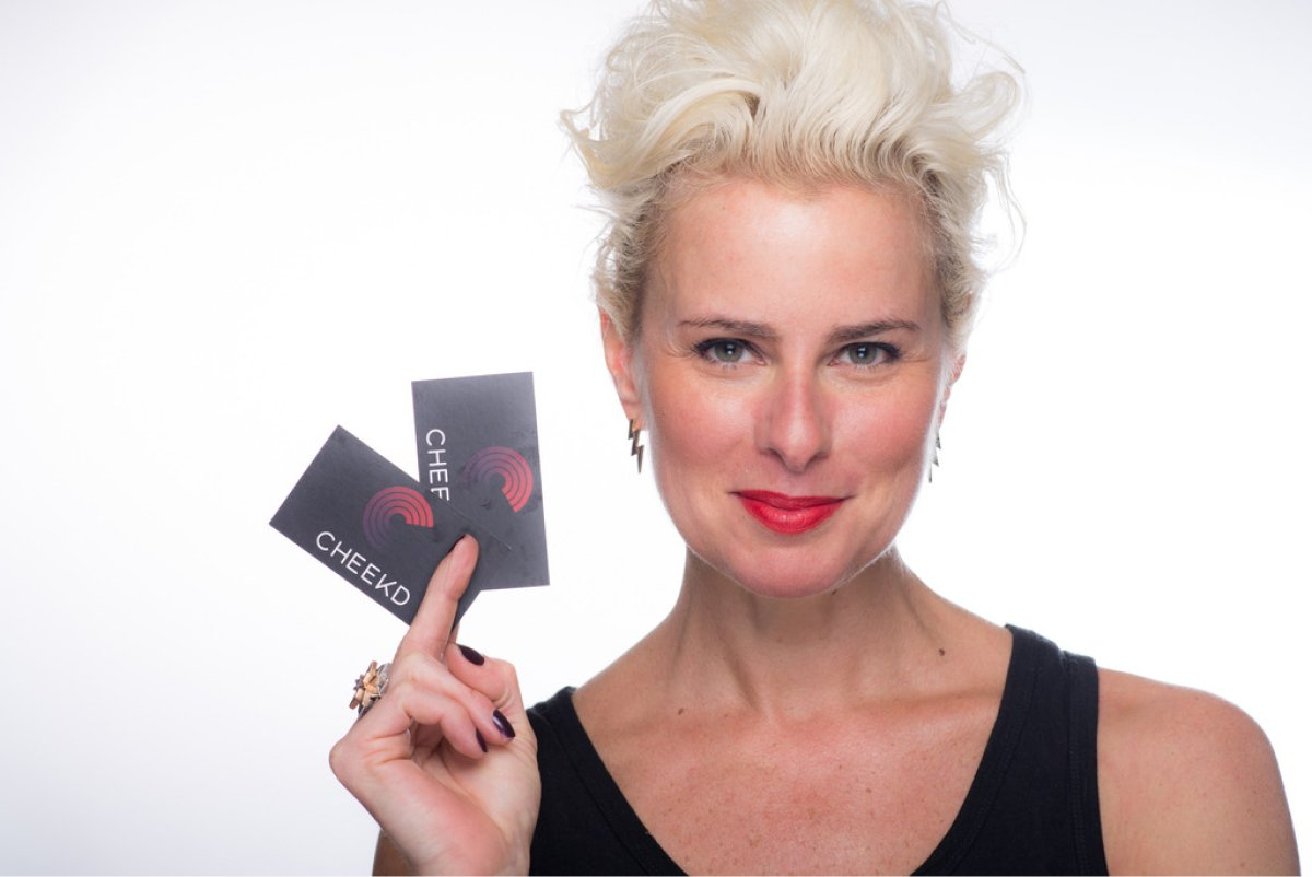 A photo of entrepreneur Lori Cheek holding a couple business cards in her hand.