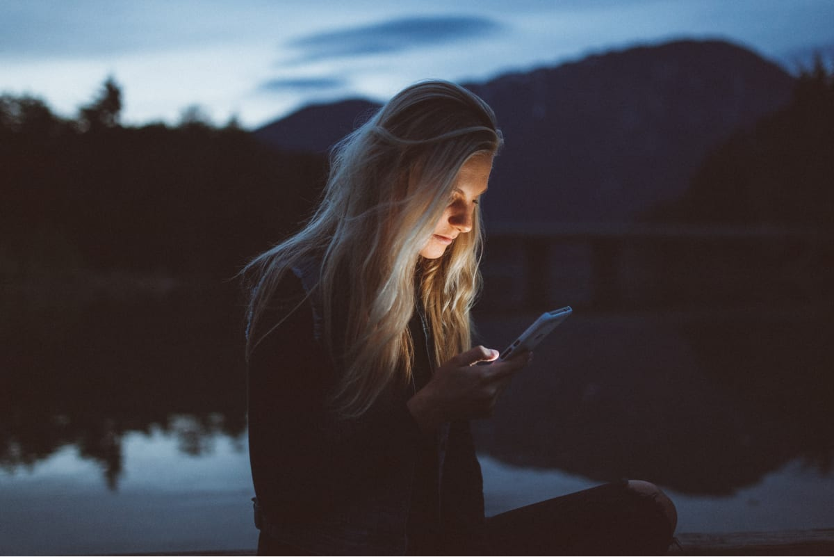 A photo of a woman sitting by the water, checking a mobile app on her smartphone.
