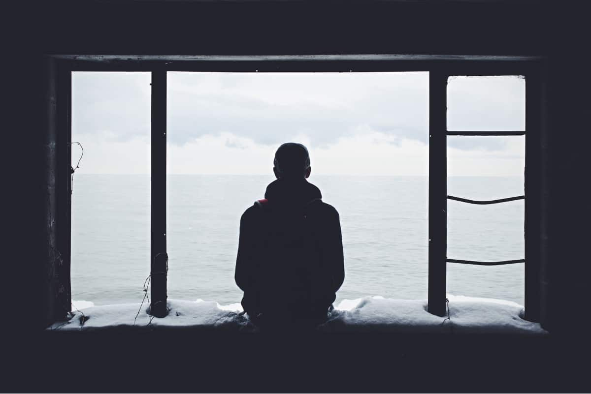 A photo of a person sitting on a snowy windowsill, overlooking a body of water.