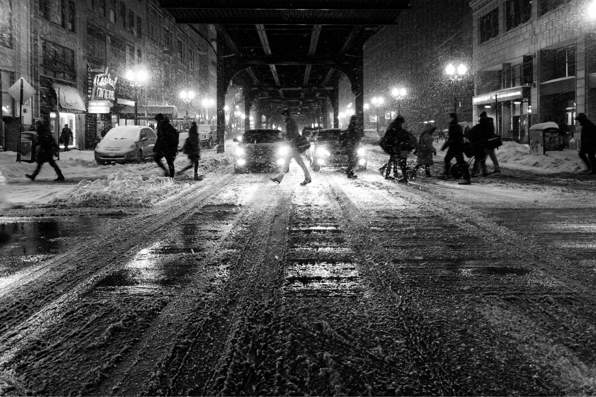 A photo of people crossing a snowy street during the winter time.