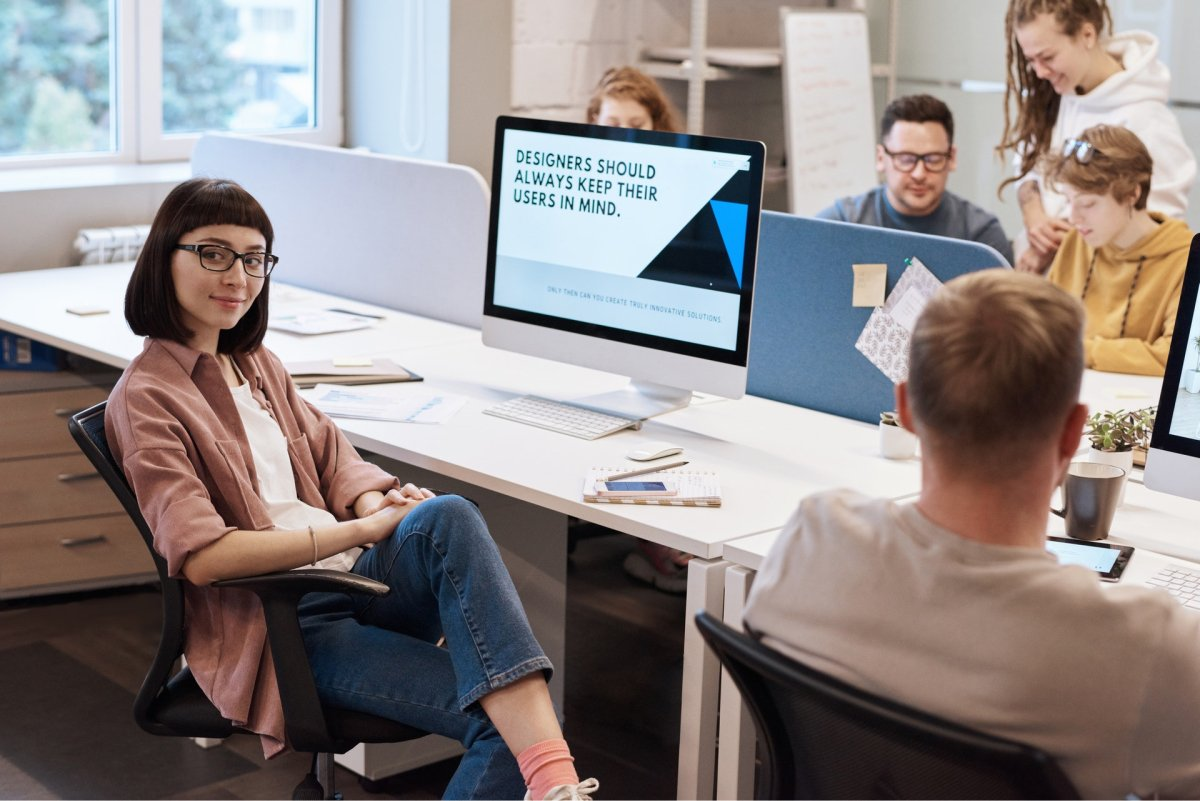 A design team sitting together with a design quote on a woman's computer monitor.